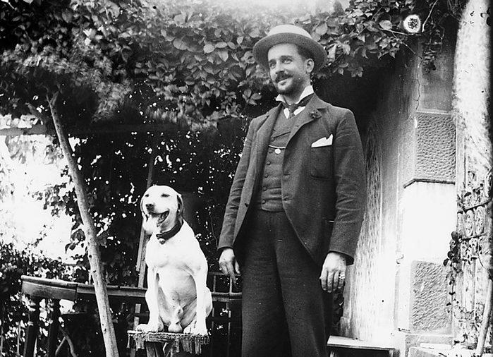 Uomo in abito borghese e cappello col cane in posa in cortile