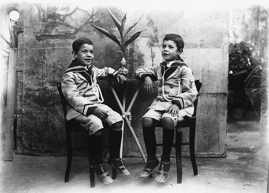 Due fratellini in abito alla marinara identico seduti a tavolino
