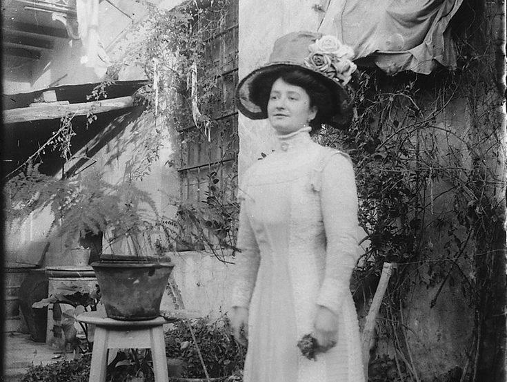 Elegante signora con vistoso cappello in giardino